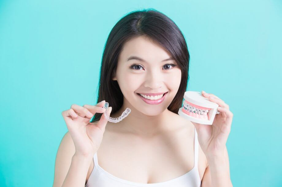 Smiling Girl Holding Invisalign Clear Braces